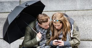 Photo of a teenage girl and guy looking at a cell phone.