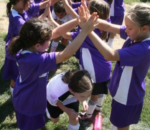 A photo of young girls dressed in soccer uniforms forming a tunnel with their hands for which other girls run through as a post-game ritual.