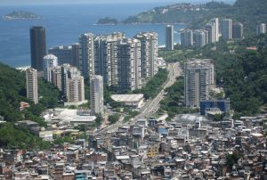 This photo is of a city with large high rises in the background and a slum in the foreground