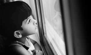 This photo depicts a young boy with dark hair looking out the window