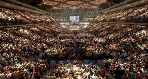 A photo of thousands of people in a stadium during a megachurch ceremony