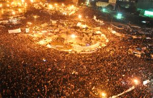 Photo of a crowded Tahirir Square in Cairo, Egypt where many people in the crowd are waiving Egyptian flags in the air.