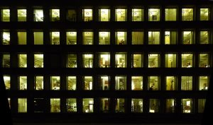 A photo of a large office building at night where you can see many people working inside after hours