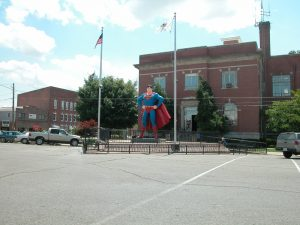 A statue of Superman between two flagpoles and in front of a two-story brick building is shown.