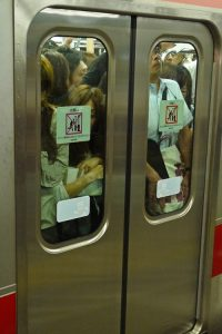 A crowd of people behind closed subway car doors is shown
