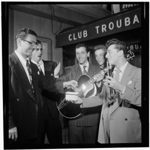 A group of young men wearing suits, including a guitarist, are shown in a black and white photograph in front of the awning of a nightclub.