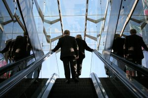A man and a woman, both wearing business suits, are shown from behind at the top of an escalator.