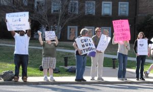 A group of people are shown standing on a sidewalk holding protest signs.