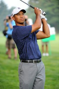 A photo of golfer Tiger Woofs holding his club up in the air on the golf course after hitting a golf ball