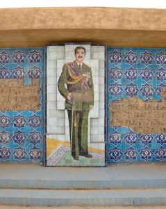 A mosaic of Saddam Hussein and other tile decorations are shown on a wall