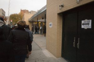 """People are shown standing outside a building in line. Signs on the building read """"vote here"""" in various languages"""