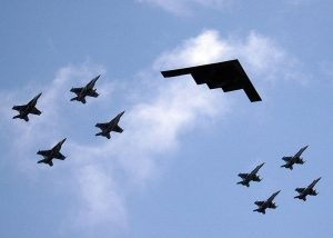 A formation of airplanes featuring fighter jets and a stealth bomber is shown in the sky