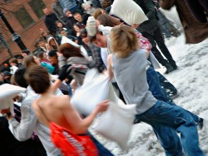 People having a pillow fight outdoors are shown here