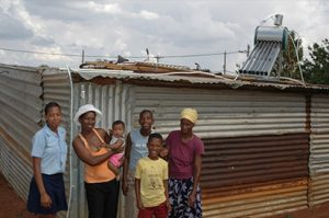 A photo of a family of villagers in Africa in front of a solar panel on top of a roof