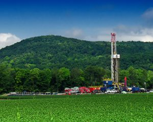 This is a photo of a shale drilling platform below a forested hill