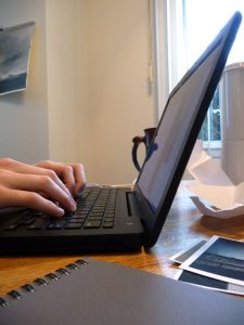 A person shown from above holding a laptop.
