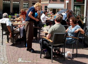 Waitress serves customers in an outdoor cafe.