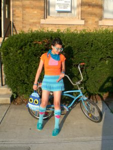 A young woman in brightly colored clothes are carrying an owl handbag is shown standing in front of a vintage blue bicycle, a large hedge, and a town house.