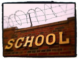 "A brick wall is shown with the word ""school"" on it and barbed wire on top"