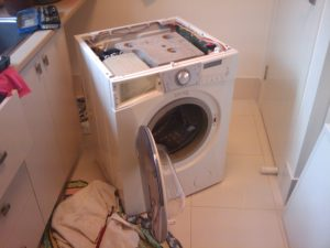A broken washing machine is shown with no top cover