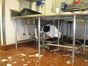 A man is shown scrubbing floors and walls beneath a group of sinks in a restaurant kitchen.