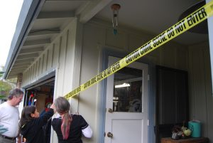 People placing crime scene tape around a house