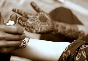 The photo shows a woman's hands being covered in intricate henna designs