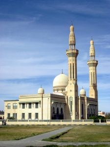 A mosque is shown, a large building with one large dome and two smaller domes and two towers, called minarets
