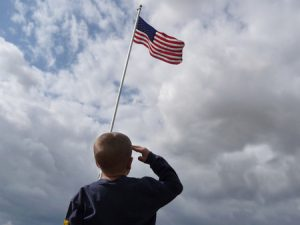 A young boy is shown from behind saluting the American Flag flying from a flagpole