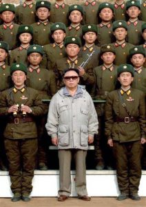 Kim Jong-Il of North Korea is shown wearing sunglasses amid a group of uniformed North Korean soldiers
