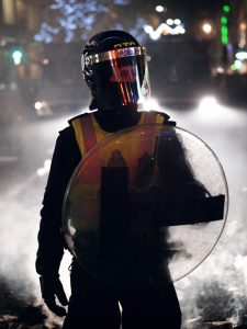 A masked officer with a shield is shown here