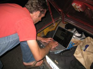 A man leaning over a laptop, typing is pictured here
