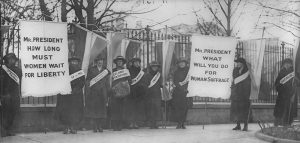 Figure (a) shows women's suffrage marchers