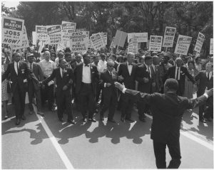 Figure (b) shows a large group of marchers for civil rights