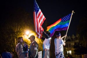 Figure (c) shows people waving a U.S. flag and a rainbow flag